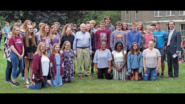 """Mr. Frank Grunwald, survivor of Auschwitz, along with his wife, Barbara, pose for a photo with the Winamac Community High School cast of the 2019 fall play, """"And Then They Came for Me: Remembering the World of Anne Frank."""" Photo by Sophie Dickinson"""