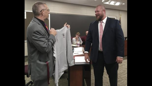 Eastern Pulaski Community School Corporation Superintendent Dan Foster gave Jeremy Tucker a Warrior shirt. Tucker was hired as the new high school principal.